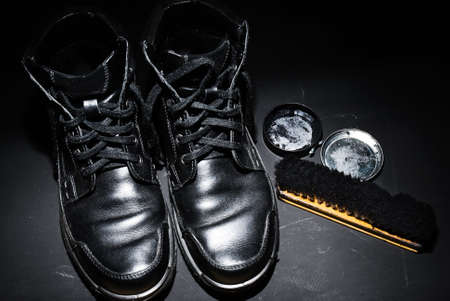 Pair of black male shoes with shoe polish and brush