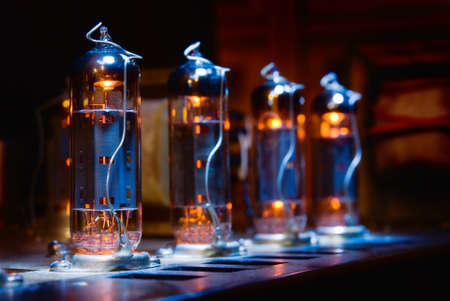 Set of glowing vintage guitar amplifier vacuum electron tubes Фото со стока