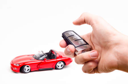 Modern car key in hand and a red car in the background Stock Photo
