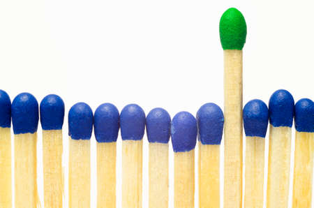 Row of matches with the head in blue color, one longer with a green head