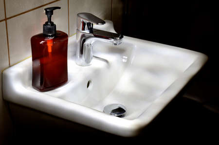 liquid soap: Contemporary bathroom basin with bottle of liquid soap