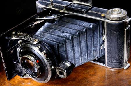 folding camera: Close up of antique bellows camera on mahogany table