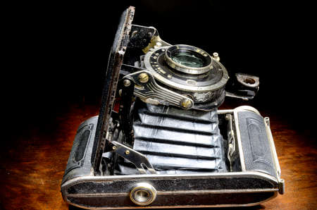 Not fully retracted antique bellows camera on mahogany table Stock Photo