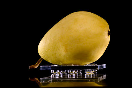 Pear placed on a tray, with black background