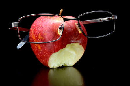 Bite on apple with glasses on black background Stock Photo