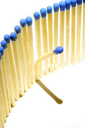 Matchsticks in a row with one leaned over, on white background