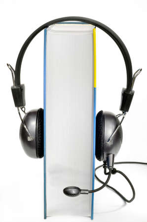 Headphones with microphone worn by book on white background Stock Photo