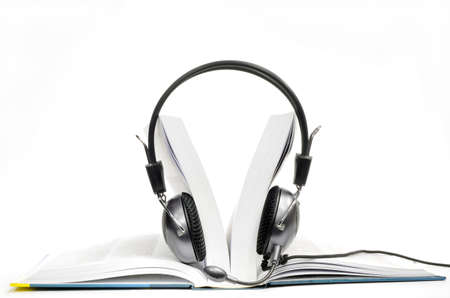 Headphones with microphone worn by opened book on white background