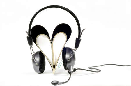 Headphones with microphone worn by magazine in heart shape on white background