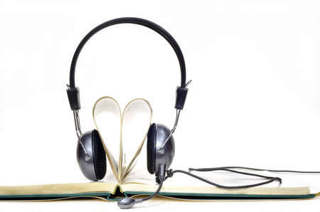 Headphones with microphone worn by pages curled into heart shape on white background