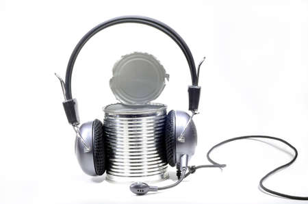 Headphones with microphone worn by opened can on white background