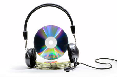 Headphones with microphone worn by compact discs stack on white background