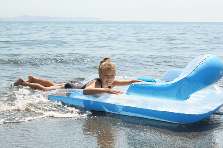 Girl of seven years on  inflatable mattress in  sea photo