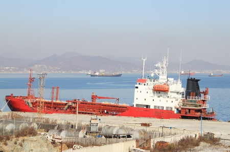 raid: Red tanker standing at  old mooring against  ships on raid Stock Photo