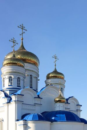 Gold domes and crosses of orthodox temple against  blue sky photo