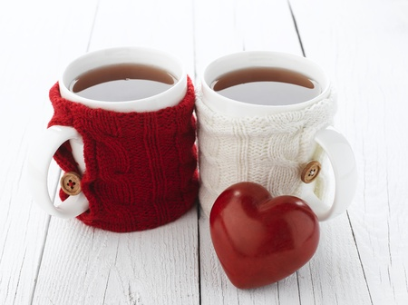 upperdeck view: Two warm cups of tea with red and white knitted thing on it and with heart for Valentines day Stock Photo