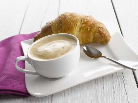 capuccino: Capuccino coffee cup with croissant on white table Stock Photo