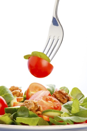 nature photography: Close-up of salad on a fork over a bowl of salad, isolated on a white background.