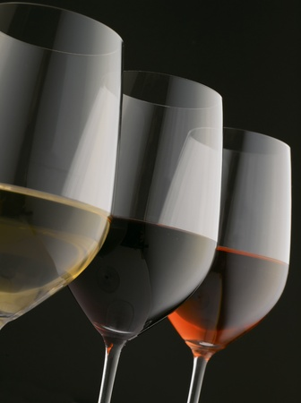 winetasting: Glasses of red, white and rose wine on black background (Shallow focus. Focus on red wine)