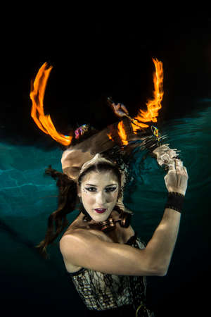 horn like: Girl posing underwater with fire Loks like a horn Stock Photo