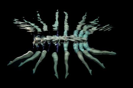 Synchroniseerde zwemmer nemen onderwater pose Stockfoto