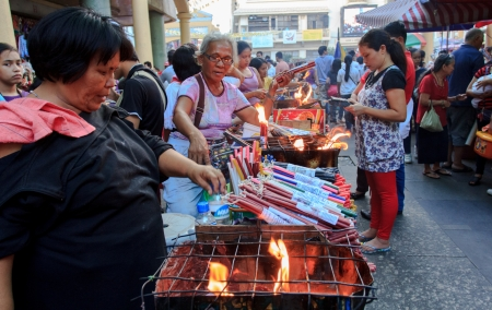 catholic mass: Quiapo, Philippines - January 6, 2013: Vendors selling assorted colored candles during the first Sunday Catholic mass before the celebration of the feast of Black Nazarene