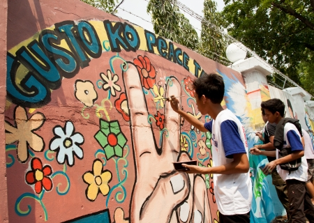 surpassing: Quezon City, Philippines - June 1, 2013: An attempt to make 3,770 meters of peace mural along the major national highway in Manila, which will be considered the longest peace mural in the world surpassing the Guinness record Chile Wall of Peace. Editorial