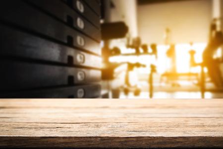 espacio en el escritorio de madera sobre el gimnasio de fitness y mano abierta al escritorio vacío. Para el montaje de exposición de productos. Presentación del asunto.