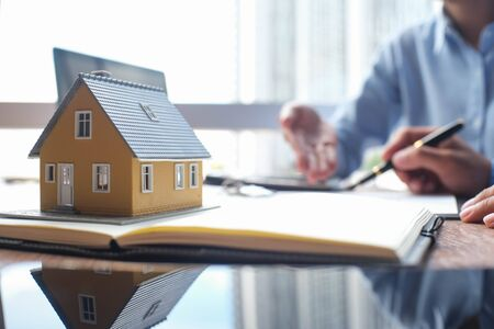 House model and business Insurance authorities showing an insurance policy and dealing the policyholder must to sign