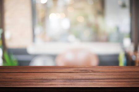 Espacio de escritorio de madera vacío y fondo borroso del tono vintage del restaurante para el montaje de exhibición del producto