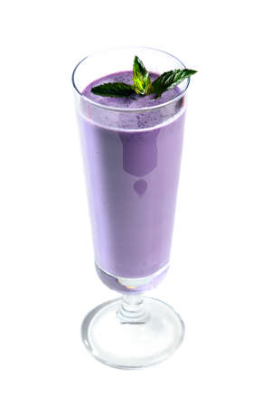 Blueberry milk shake in clear tall glass garnished with mint on white background