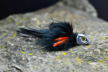 Black-orange jig streamer made of feathers with a fish-shaped load on a gray background