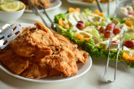 Fried pork and chicken cutlets in a wedding banquet with cheese and salad in the background 免版税图像