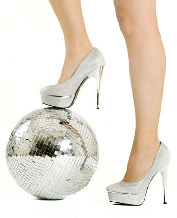 Women's foot in a formal shoe leaning against a disco ball on a white background