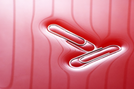 two office paper clips on red background Stock Photo - 11015507