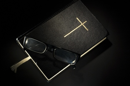 Bible with eyeglasses and bookmark. Black background Stock Photo