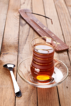Turkish apple tea in traditional glass and plate on wooden background