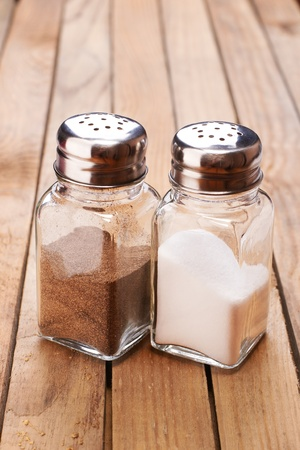 Salt and black pepper in shakers closeup on wooden background