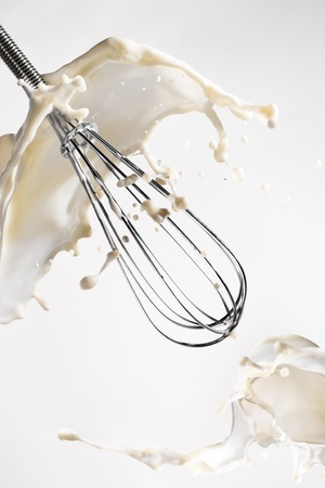 Steel whisk in splash of milk on white background Stock Photo