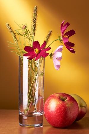 Natura morta con fiori e mele su sfondo giallo Archivio Fotografico