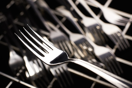 Fork on set of forks background. Selective focus