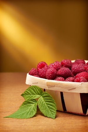 Fresh raspberries in the basket on yellow background Stock Photo - 11136281
