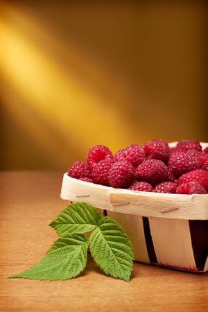 bushel: Fresh raspberries in the basket on yellow background