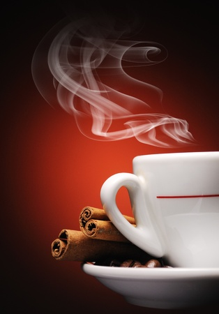 Steaming cup of coffee, cinnamon sticks and coffee beans.