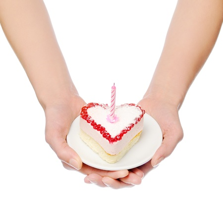 Female hands keep heart-shape cake with candle. Isolated on white Stock Photo