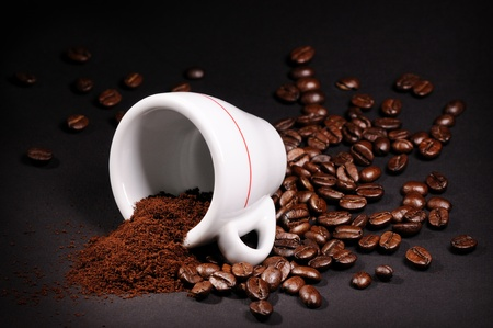 grinded: Cup with heap of coffee beans on black background