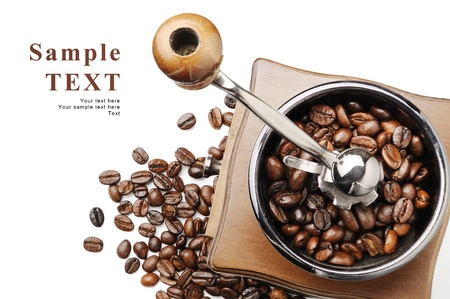 Old coffee grinder and coffee beans on white background with space for your text