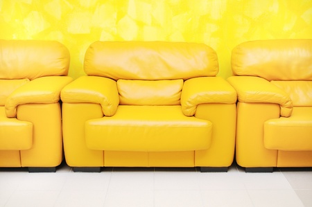 Yellow leather armchairs in waiting room and yellow textured wall photo