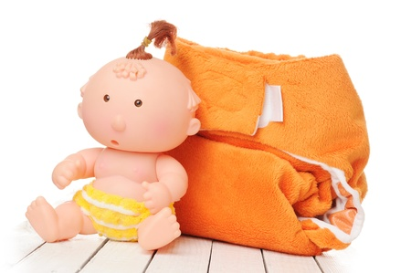 washable: Orange cloth diaper with toy isolated on white background