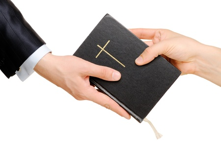 Hand giving the Bible to another person  Isolated on white photo